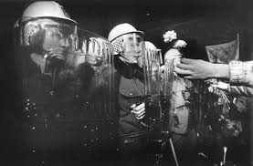 Protesters place flowers in the shields of armed police during the revolution of 1989, Prague, Czechoslovakia